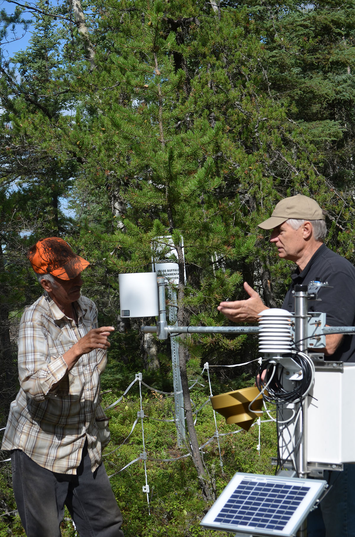 Howard Lacorde (left) and Kevin Percy (right) discuss the passive air monitoring and meteorological equipment at one of five monitored Berry Focus Group berry patches.